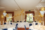 wedding reception decorated with table decorations and balloon arches
